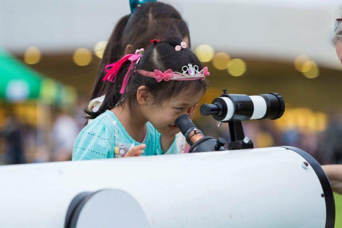 Child looking in telescope.